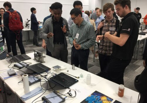 A group of male researchers stood in front of desk with laptops and other equipment on it, having a discussion.
